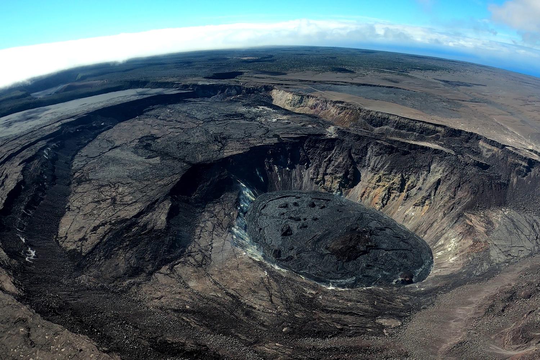 Steep cliffs surround the summit caldera, which has no hardened into black rock