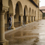 A student stays sheltered in the arcade as he pauses to watch the rain in the Main Quad.
