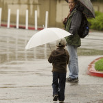 Stanford staff member Mike Ling walks across campus with his son Hudson, 3. The younger Ling had a day off from school when it was cancelled for the day because of rain.