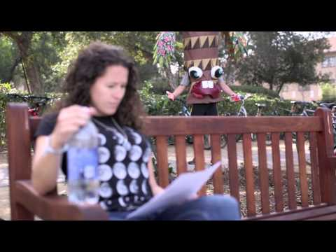 Video still image of a woman sitting on a bench reading. The Stanford Treeree is in the background.