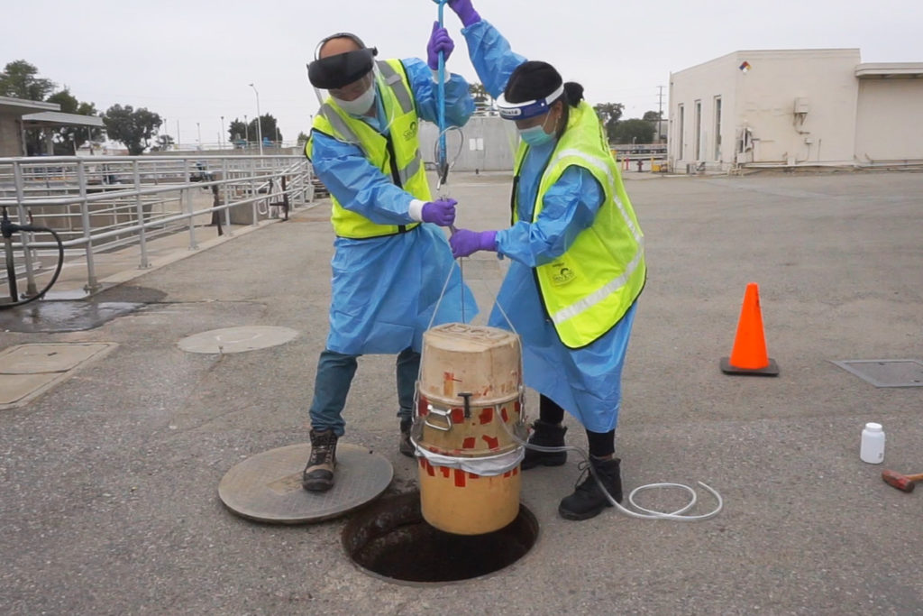 Two people in protective gear holding device over a manhole
