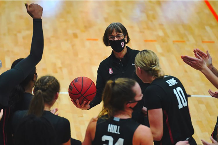 Tara VanDerveer holding a basketball with players around her.