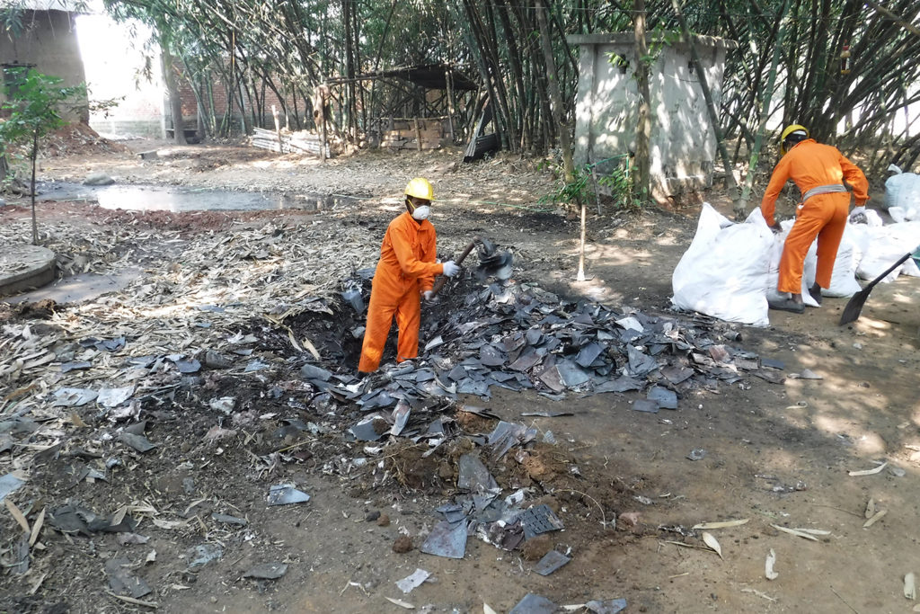 Two workers, one digging amid debris the other putting something in a garbage bag