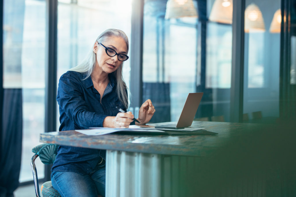 Portrait of senior woman using a laptop in an office..