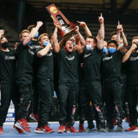Cheering men holding trophy