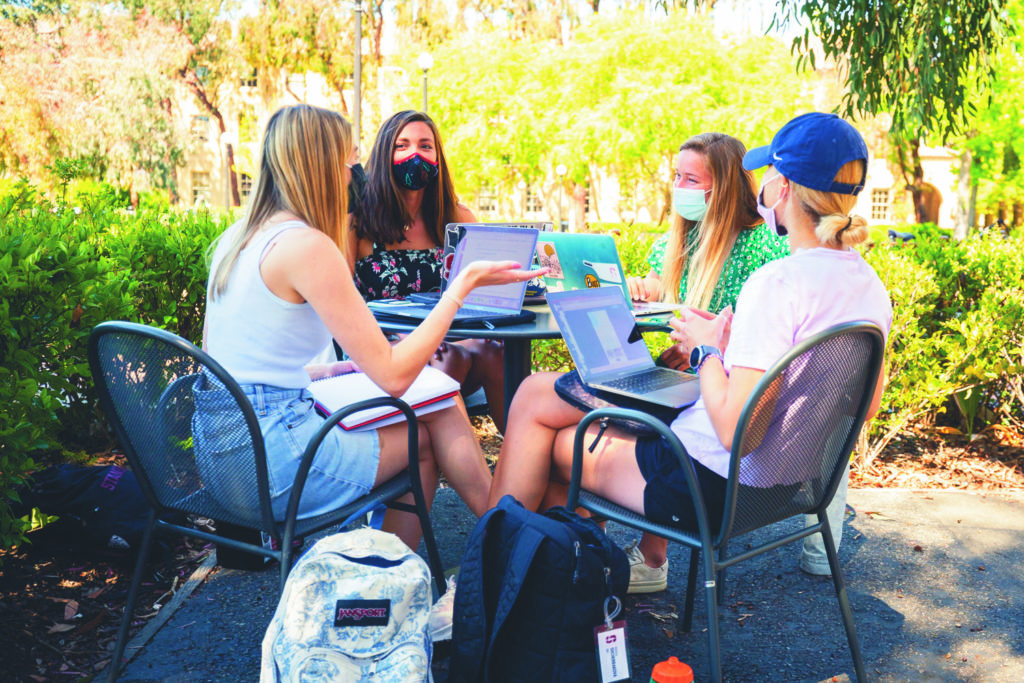 Four students seated around a table outdoors, with face coverings, in conversation