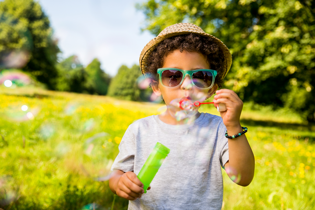 Male child wearing a hat and sunglasses blowing bubbles in a park setting.