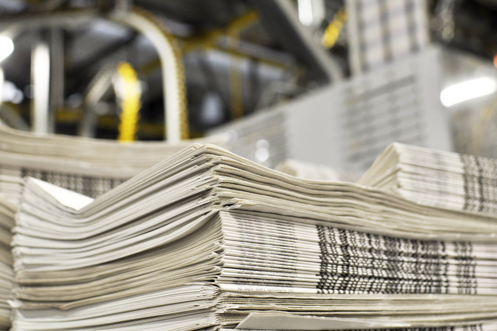 A stack of freshly printed newspapers, in the background printing machines and technical equipment.